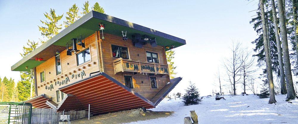Haus am Kopf auf Dach gestellt vor Winterlandschaft