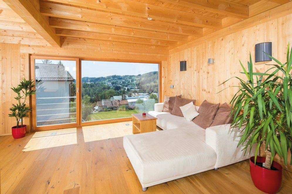 Gemütliches Wohnzimmer mit heller Couch. Zimmerpflanzen und der Ausblick durch die bodenlangen großen Balkonfenster lassen das Grüne ins Wohnzimmer.