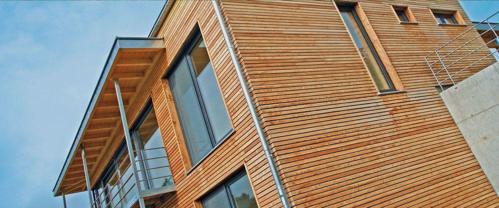 Ausschnitt Fassade eines Massivholzhauses mit großen Fensterfronten