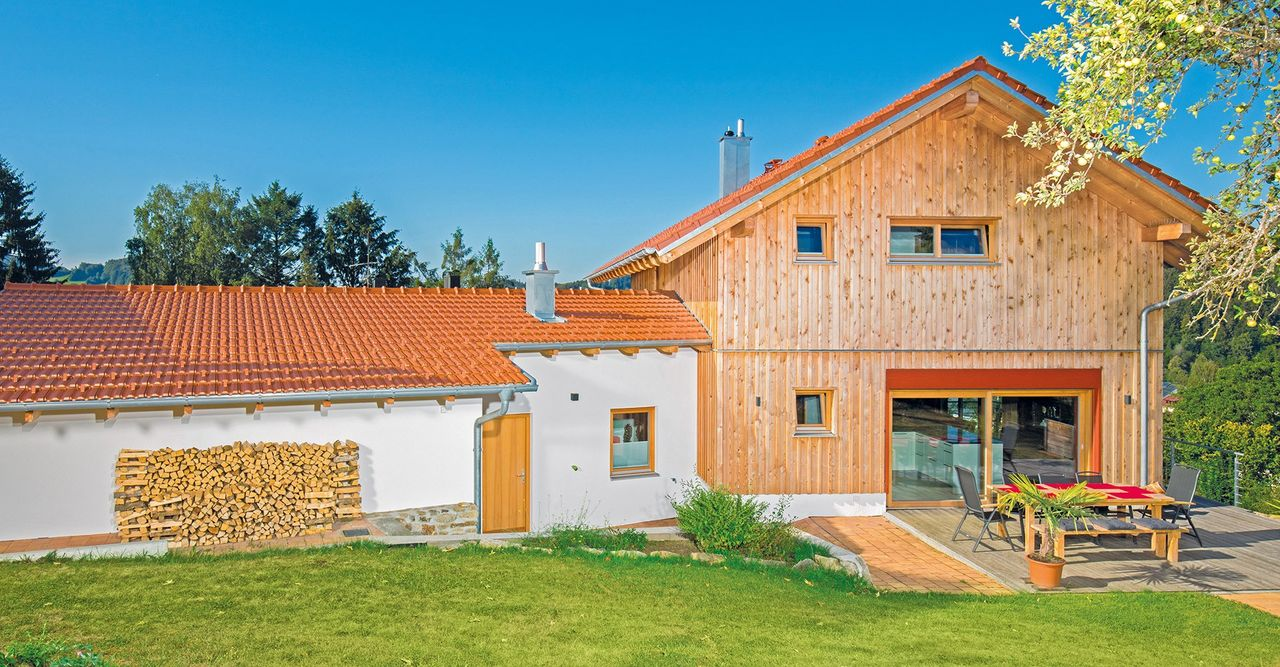 Individuelles Brunthaler Massivholzhaus mit roten Farbakzenten