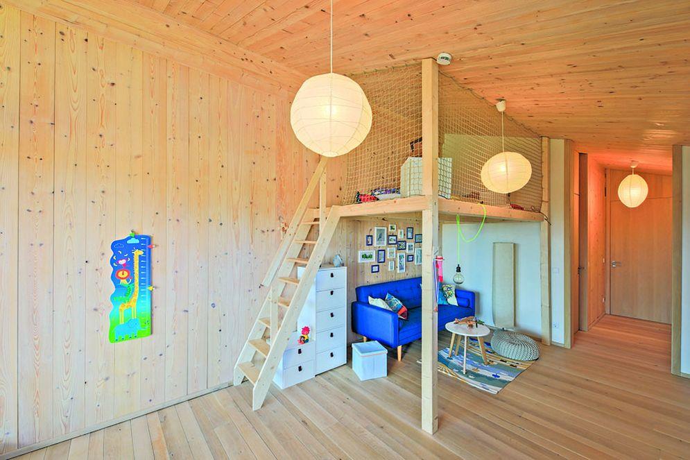Kinderzimmer im Holzhaus mit Hochbett. Eine Treppe führt zum Hochbett, das seitlich mit Netzen abgesichert ist und dadurch eine verspielte Abenteueratmosphäre erhält. Unter dem Bett sind eine blaue Couch mit Tisch, Verstaumöglichkeiten und Spielzeug.