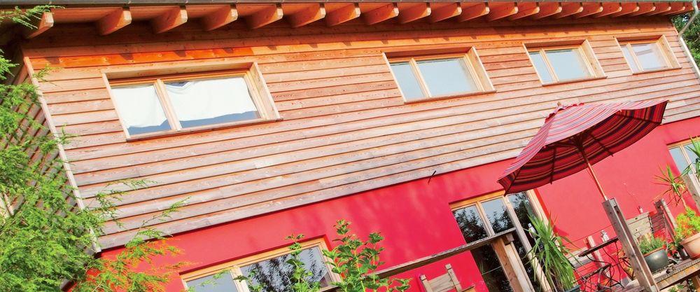Fassade Massivholzhaus mit Holzverkleidung Obergeschoss und roter gestrichener Fassade im Erdgeschoss