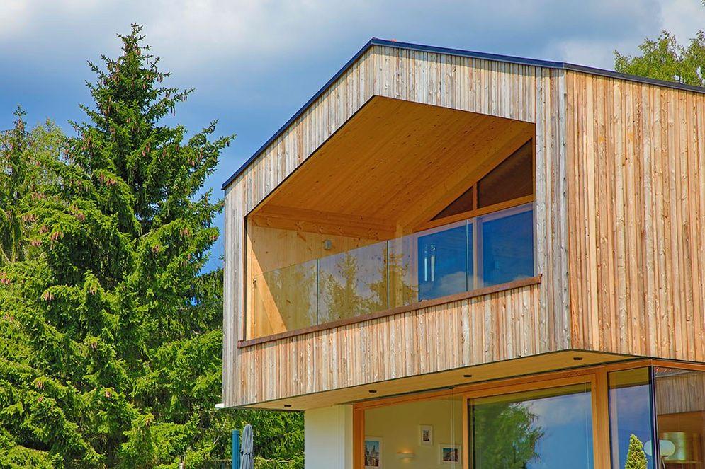 Seitliche Detailansicht des großen, überdachten Holzbalkons mit Glasgeländer.