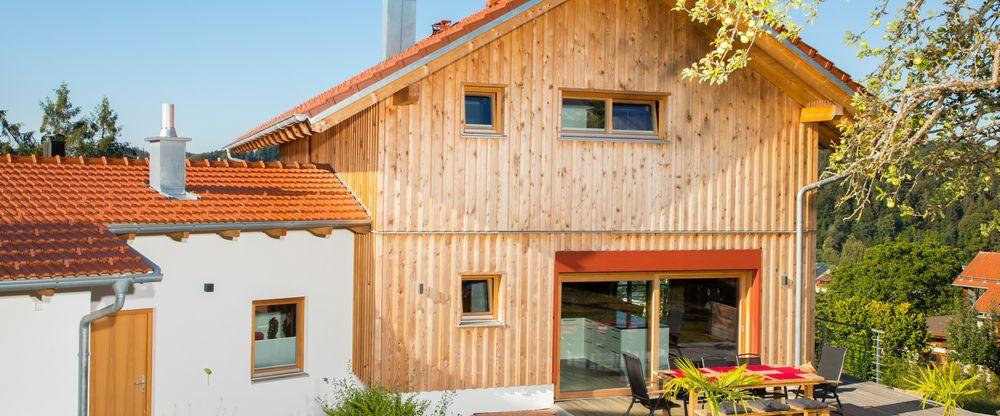 Ein Foto eines Holzhauses mit teilweise verputzter Fassade mit roten Farbakzenten