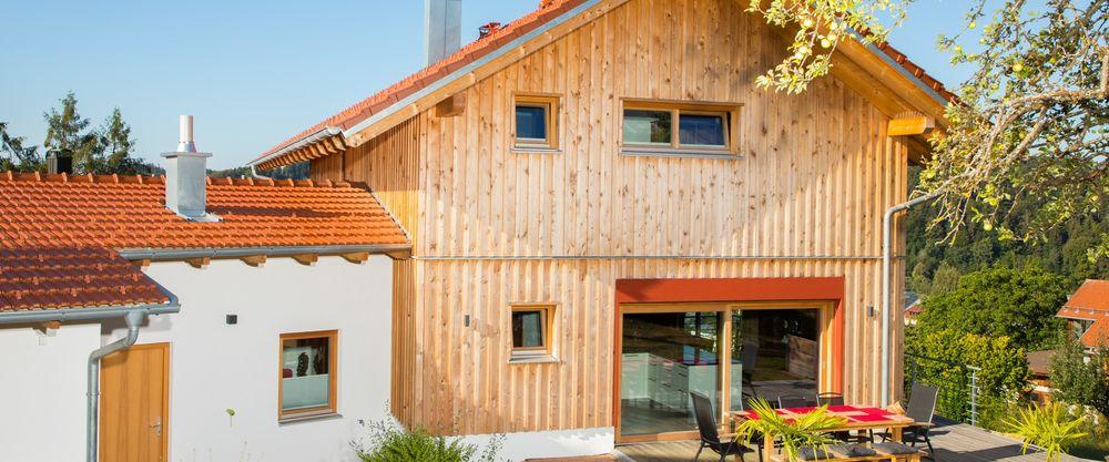 Massivholzhaus mit Holzfassade und verputzter Garage