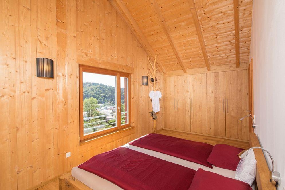 Gemütliches Schlafzimmer mit Holzinnenwänden, einem versteckten Einbau-Wandschrank und einem Fenster mit toller Aussicht.