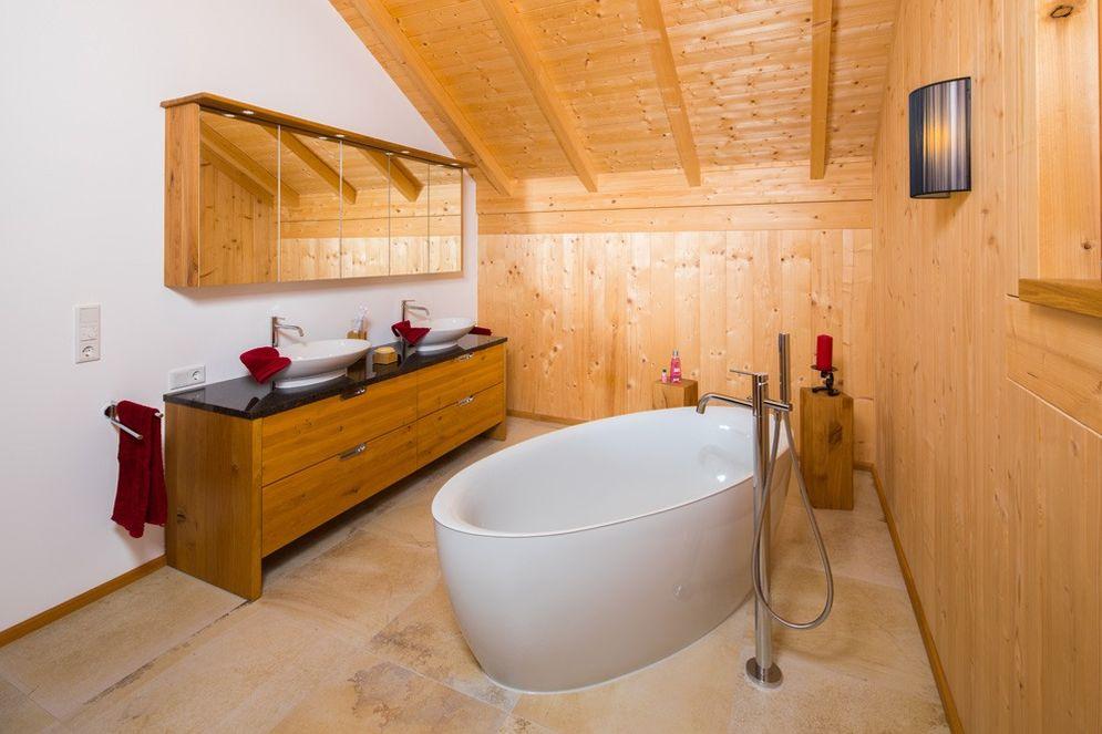 Badezimmer mit einer verputzten und vielen Holz-Innenwänden. Eine große freistehende Badewanne auf Steinboden. Viele kleine rote Akzente passen gut zur Farbe des Holzes.