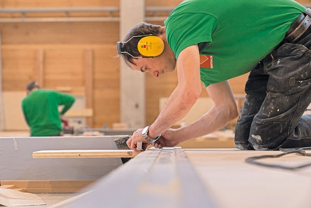 Ein Schreinergeselle in der Montagehalle der Zimmerei Brunthaler vermisst ein Holzbrett