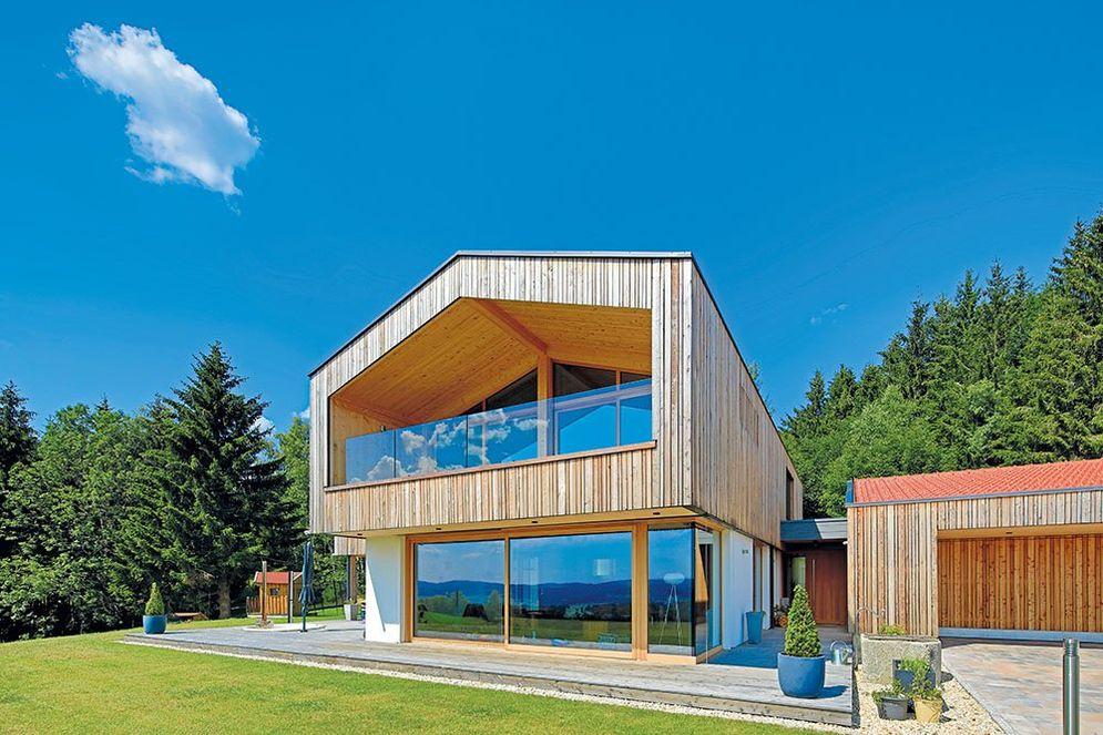 Großes Architekten-Holzhaus mit großen Fenstern von vorne mit Garten.