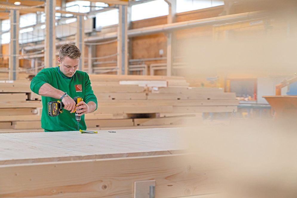 Ein Zimmerergeselle bohrt ein Loch in das Holz