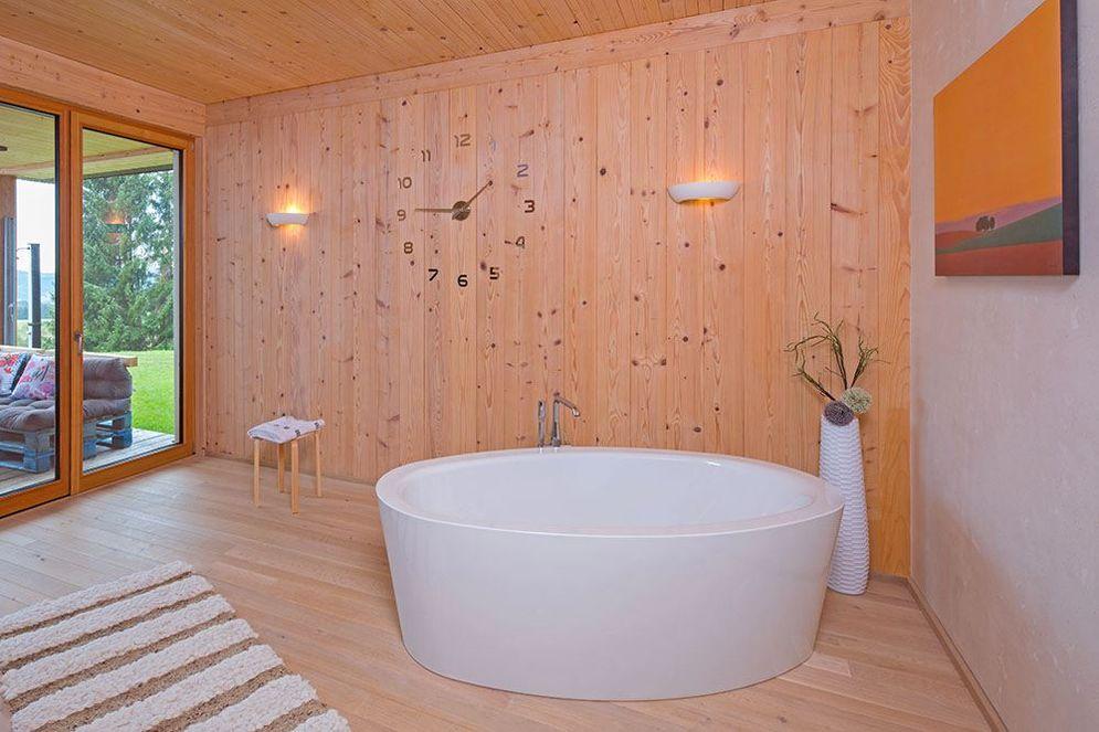 Moderne, große, freistehende Badewanne im Holzhaus mit Ausblick auf die Landschaft.