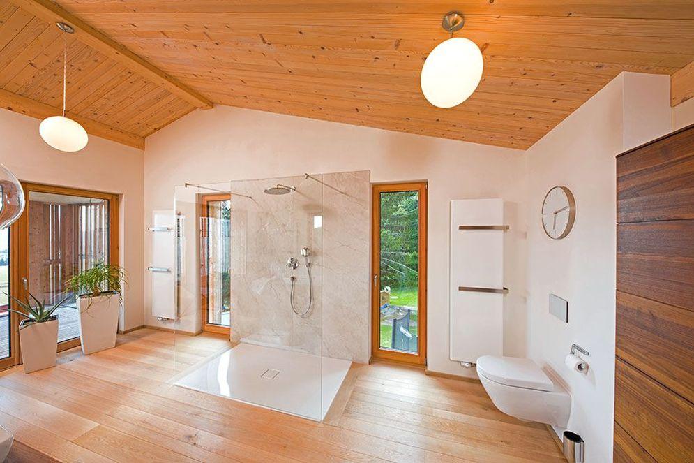 Bad im Holzhaus mit großer, offener Dusche in der Mitte des Raumes. Bodenlange Fenster bieten natürliches Licht und einen Ausblick ins Grüne.