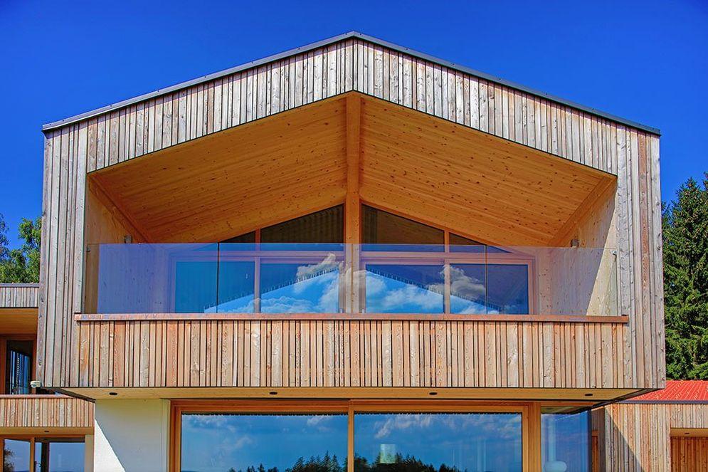 Frontale Detailansicht des modernen, überdachten Holzbalkons mit Glasgeländer.