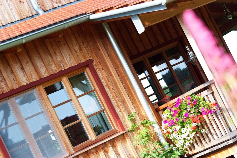 Nahaufnahme Holzfassade und Fenster und Teil von Terrasse © Brunthaler Massivholzhaus