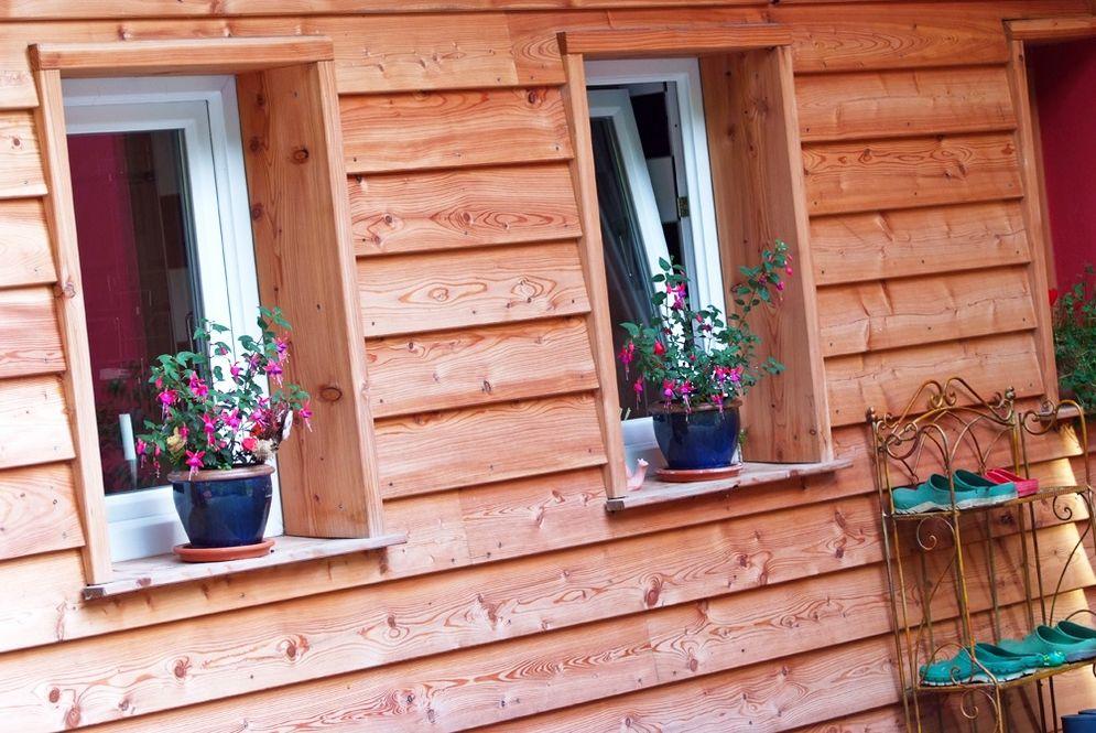 Außenansicht Holzfassade mit Fenster und Deko © Brunthaler Massivholzhaus