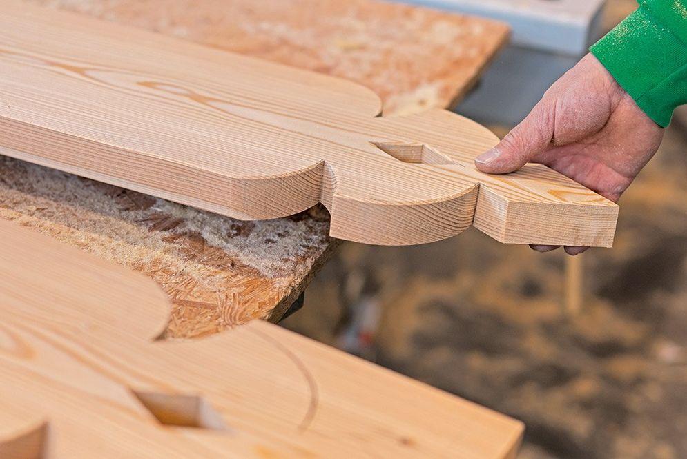 Dekorative Fassadenelemente (Pfettenbretter) werden vorgezeichnet und einzeln geschnitten und geschleift