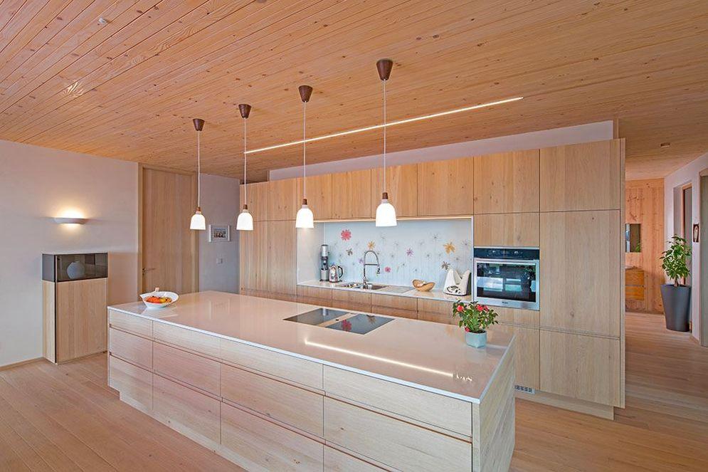 Offene Küche mit hellen Holzoberflächen, die als Raumtrenner fungiert. Eine große Kücheninsel mit Herd und Kochfeldabzug nach unten bieten viel Arbeitsfläche. Der in die Decke integrierte Lichtstreifen spendet, zusätzlich zum natürlichen Licht, Helligkeit.