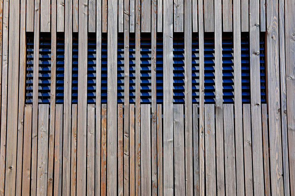 Detailansicht der Holzfassade, die durch die teilweise durchgehenden Fassadenbalken zur kreativen Abschattungsmöglichkeit eines Fensters dient.