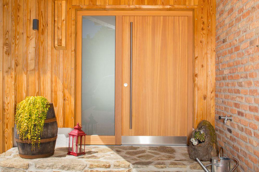 Große Eingangstür aus Holz mit Milchglasfläche daneben. Eine mit Steinen geflieste Eingangstreppe führt zur Tür. Die Wand daneben ist aus rustikalen Ziegeln.
