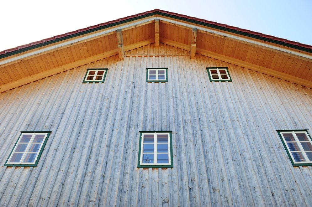 Rustikale Holzfassade mit grün-weißen Fenstern © Brunthaler Massivholzhaus