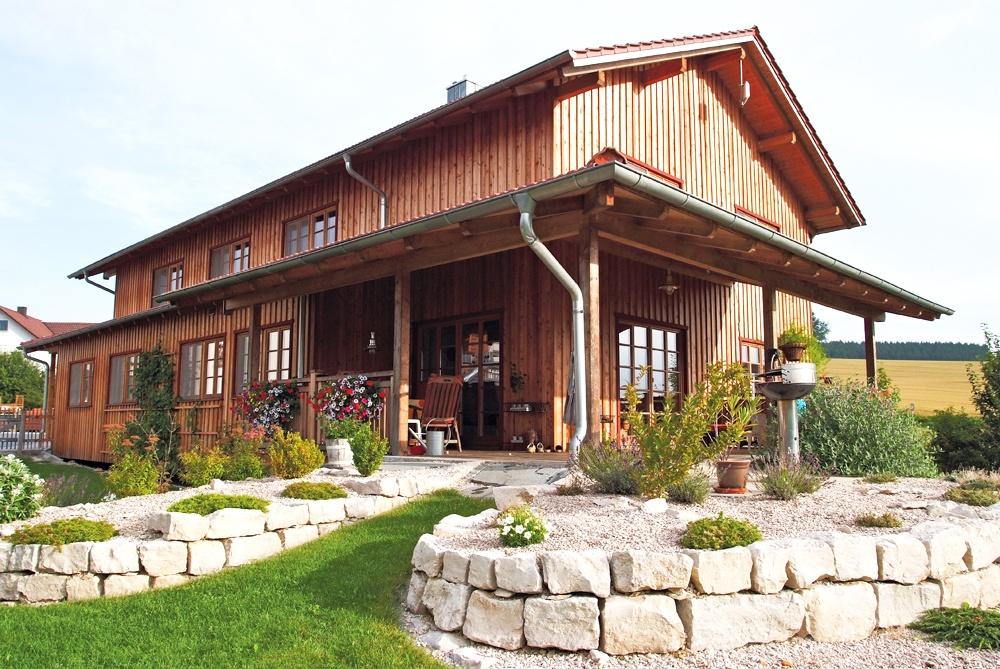 Holzhaus mit Terrasse und Steinmauer im Garten © Brunthaler Massivholzhaus
