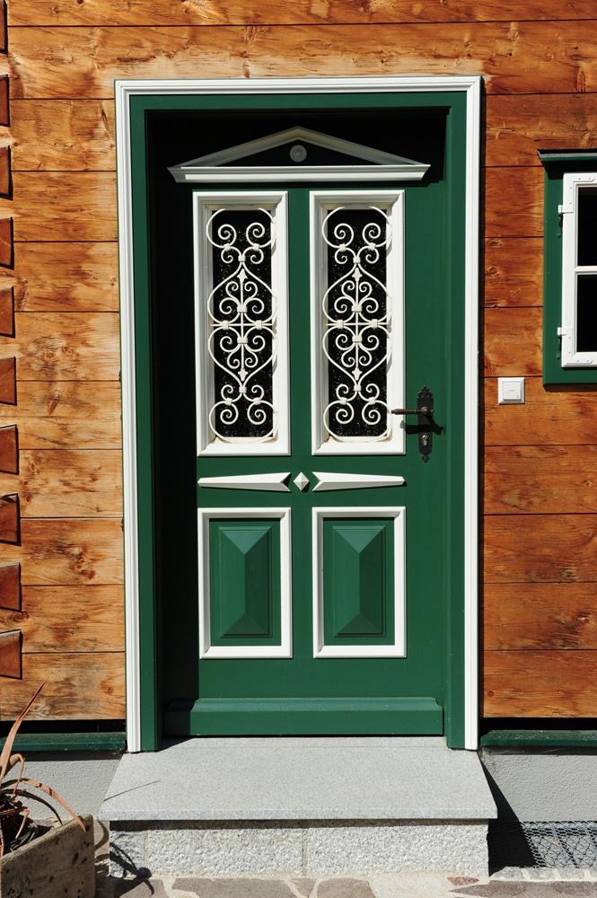 Restaurierte Holztür mit Fensterornamenten