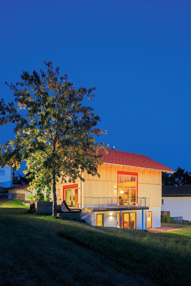 Schön beleuchtetes Holzhaus mit teils verputzter Fassade in Hanglage in der blauen Stunde am Abend.