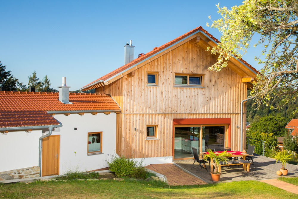Holzhaus mit Holzfassade und verputztem Anbau. Ein Baum und Esstisch mit Stühlen und einer Sitzbank auf der Terrasse im Garten.