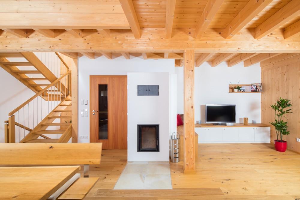 Der offene Essbereich grenzt an den Wohnzimmerbereich und den Treppenaufgang. Man sieht die massiven Holzbalken an der Decke. Ein Holzofen in der Mitte dient als Raumtrenner zum Wohnzimmer.