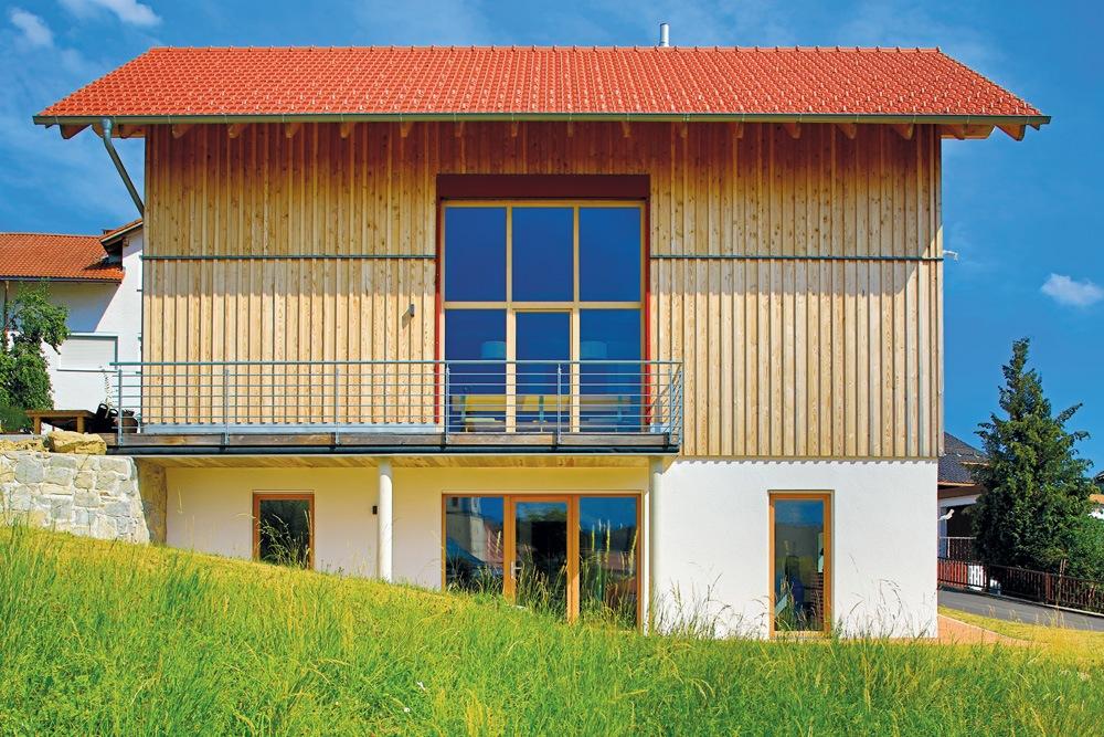 Holzhaus in Hanlage von der Seite. Die großen Fenster mit roter Umrahmung sind symmetrisch ausgerichtet.