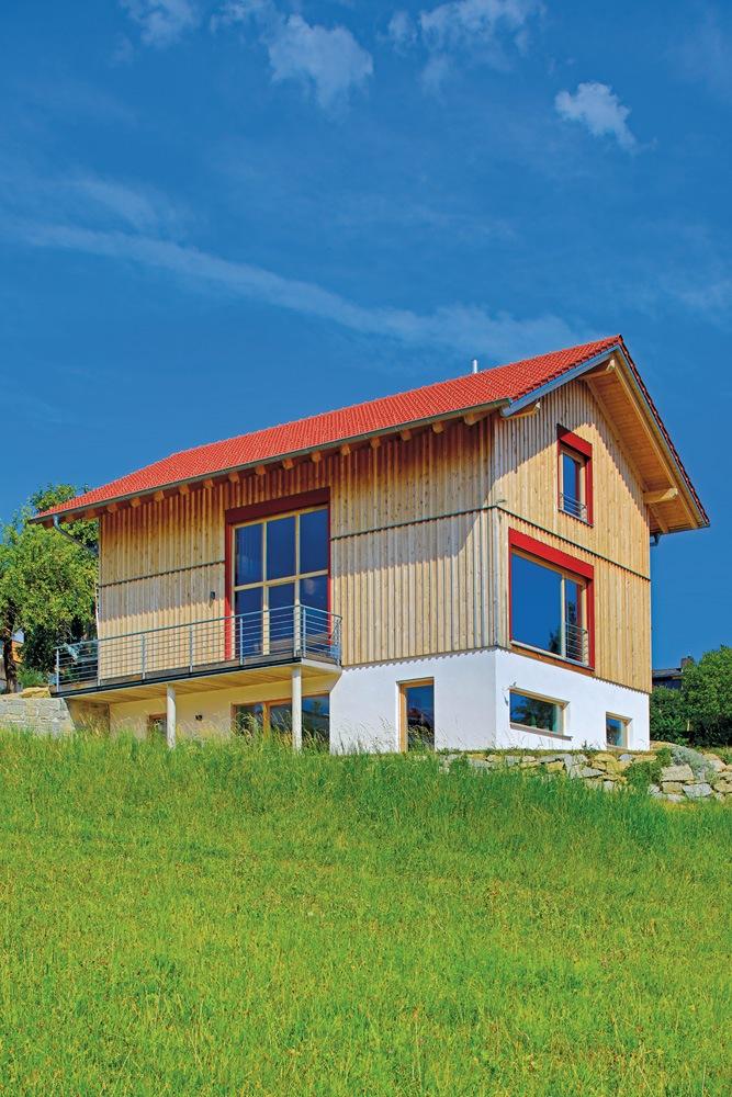 Holzhaus mit Holzfassade und großen rot umrandeten Fenstern.