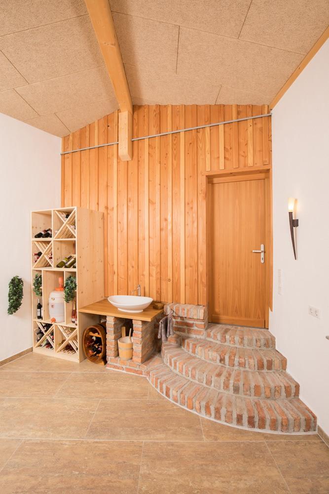 Vorraum im Anbau mit Weinregal aus Holz, einem freistehenden Waschbecken, Steinfliesen am Boden und einer rustikalen Eingangstreppe aus Ziegeln.