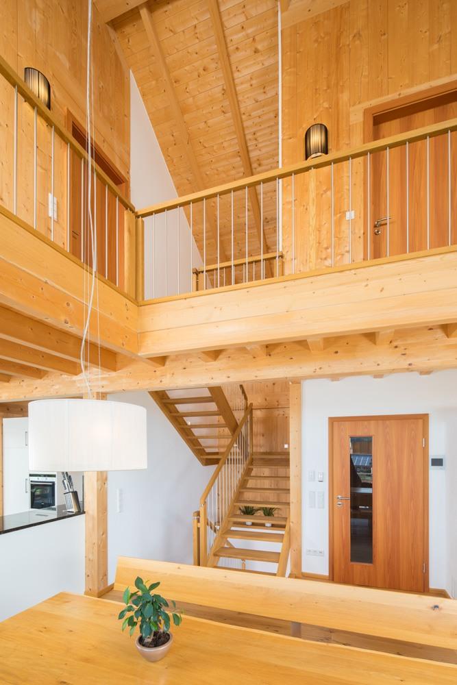Vom Essbereich sieht man die Holztreppen, die zum oberen Bereich führt. Der obere Stock ist über die Galerie sichtbar.