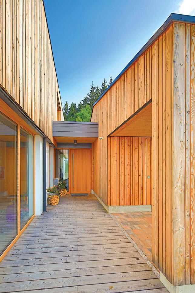 Eingangsbereich aus Holz mit Eingangstür zwischen Haus und der Garage.