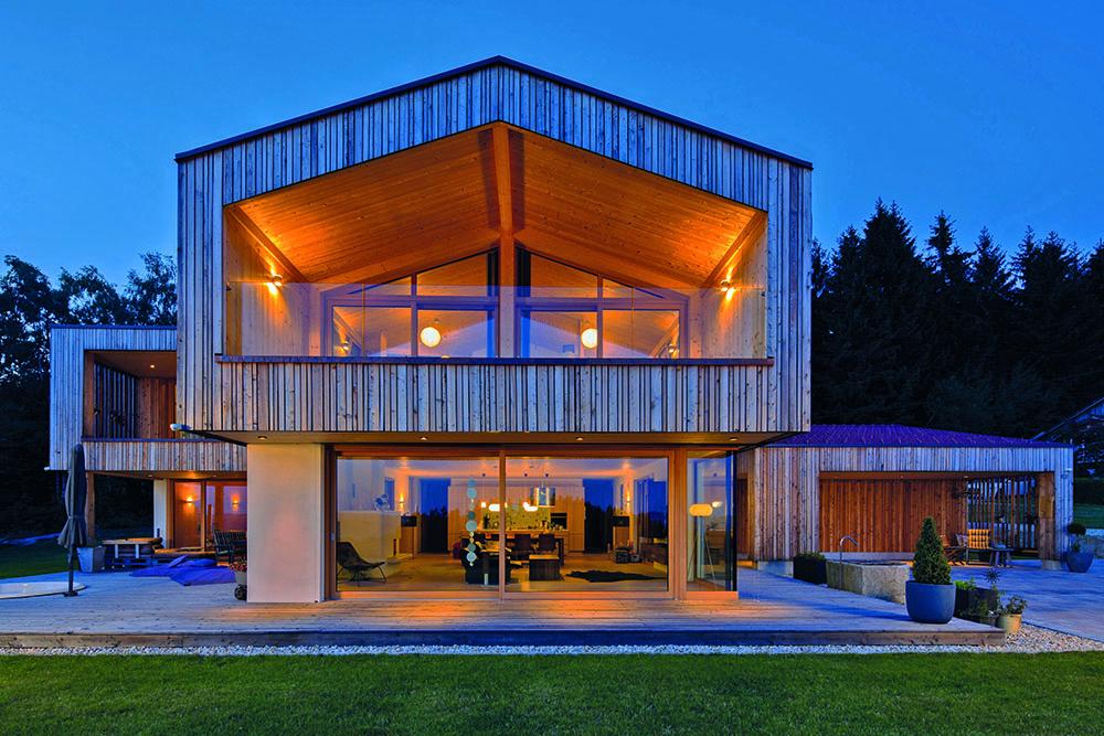 Frontalansicht des Holzhauses in der blauen Stunde. Die erleuchteten Innenräume sind durch die großen Fenster sichtbar.