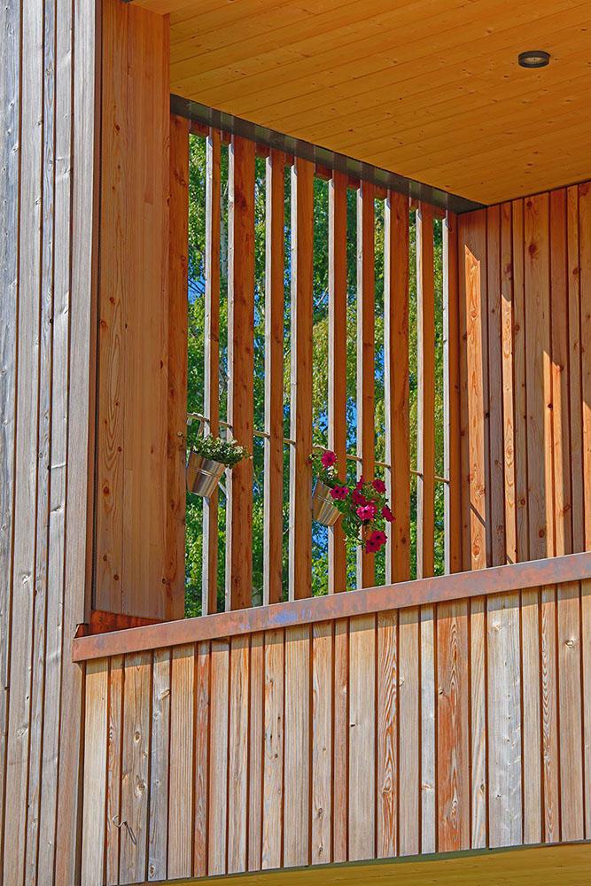 Detailaufnahme des Balkons mit Blumen. Die Sonne scheint durch die Holzbalken.