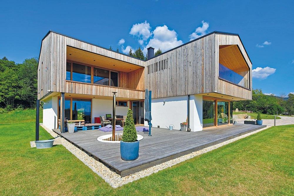 Komplettansicht des großen Hauses mit Holzfassade und verputzter Fassade. Vor dem Haus sieht man eine große Holzterrasse.