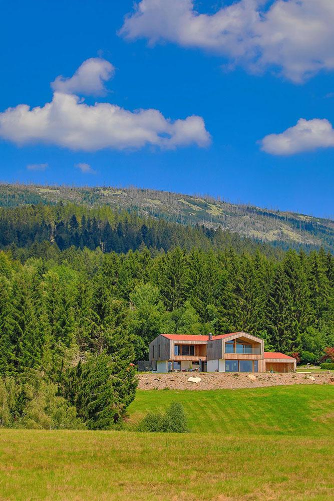 Fernaufnahme des Holzhauses mit einem idyllischen, bewaldeten Hügel im Hintergrund und Wiesen im Vordergrund.