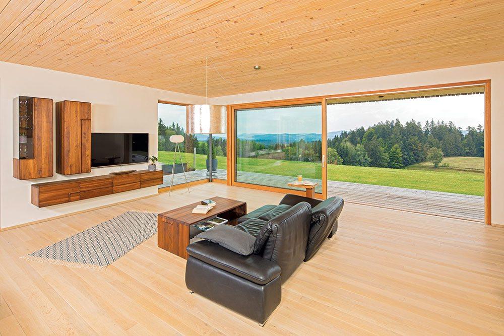 Geräumiges, offenes und modernes Wohnzimmer mit dunkler Ledercouch, Holztisch und TV-Regalen aus Holz. Bodenlange große Terrassentüren bieten einen tollen Blick auf die Wiesen und Wälder um das Haus.