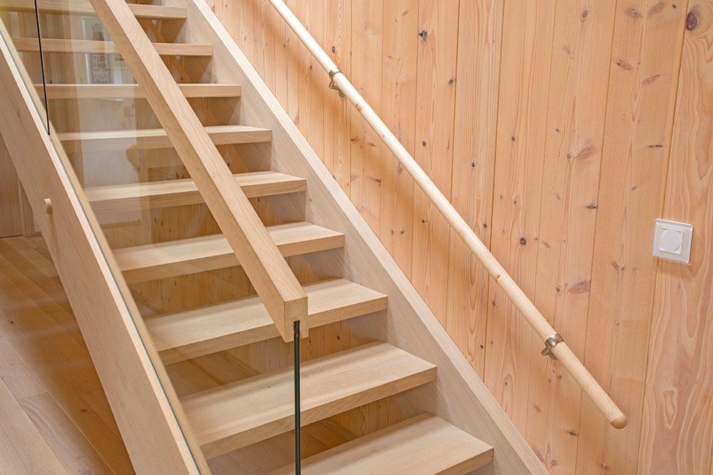 Nahaufnahme der Holztreppe mit Glasgeländer und niedrigem Handlauf für Kinder.