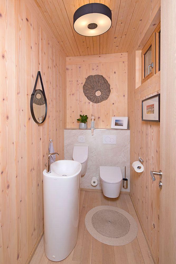 Modernes Klo mit Holz-Innenwänden. Mit Waschbecken und Pissoir.