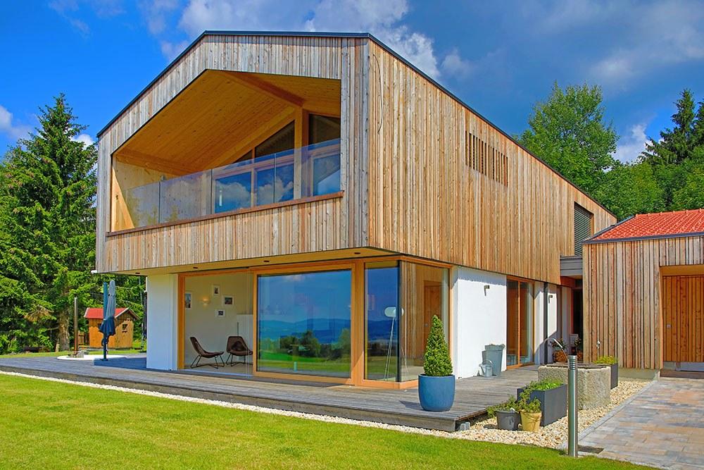 Holzhaus mit Holzfassade und verputzterfassade von Vorne. Sicht auf die Terrasse und das Wohnzimmer durch die geöffnete große Terrassentür.