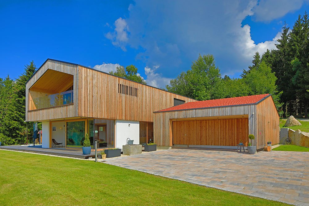 Komplettansicht des Holzhauses mit Holzgarage und Steinfliesen in der großen Einfahrt.