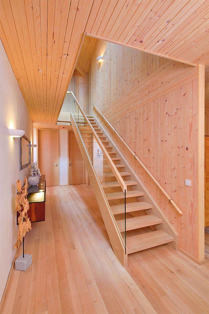 Schön dekorierter Flur und Treppenaufgang mit Holztreppe und Glasgeländer. Zusätzlich gibt es noch ein niedrigeren Handlauf für Kinder.
