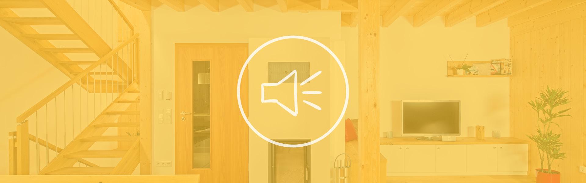 Eine Ansicht eines Wohnzimmers mit Treppenaufgang im Massivholzhaus mit einem gelben Farbton und einem Symbol für Lärm.