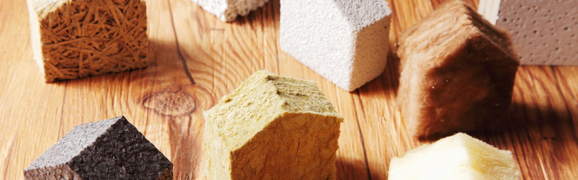 Verschiedene Dämmstoffe, die beim Hausbau verwendet werden, in Form von kleinen Häusern.