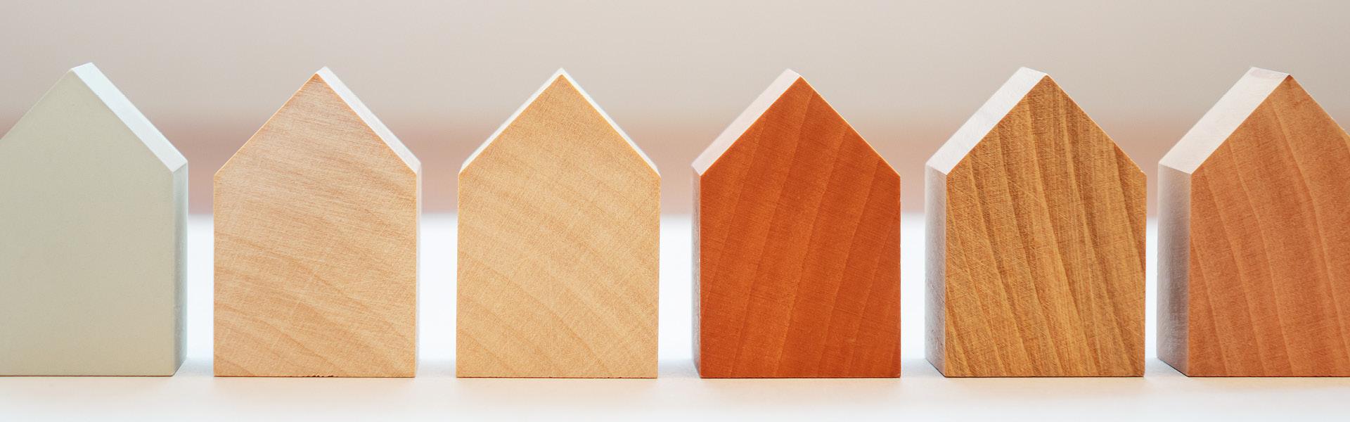 Eine Reihe kleiner Hausmodelle aus verschiedenen Holzarten.