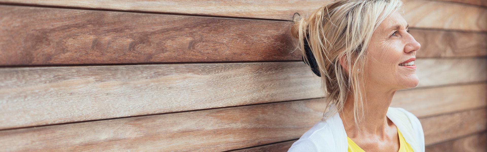 Eine Frau lehnt an einer Holzwand und blickt lächelnd in die Ferne.