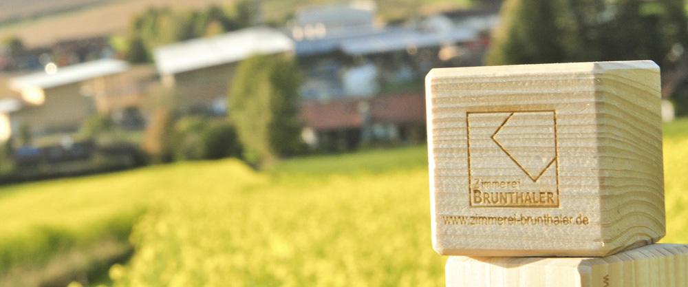 Massivholzwürfel mit Brunthaler Logo vor grüner Wiese im Hintergrund